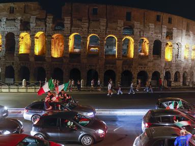 Suporter merayakan kemenangan Italia atas Inggris pada pertandingan final Euro 2020 di depan Colosseum, Roma, Italia, Senin (12/7/2021). Italia menjuarai Euro 2020 usai mengalahkan Inggris lewat drama adu penalti pada pertandingan final Euro 2020. (AP Photo/Riccardo De Luca)