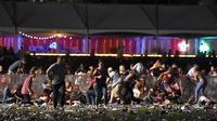 Sejumlah pengunjung berlindung saat festival musik Route 91 Harvest country setelah aksi penembakan di Las Vegas, Nevada (1/10). Pelaku penembakan disebut menembak seorang petugas keamanan dan polisi setempat. (David Becker/Getty Images/AFP)