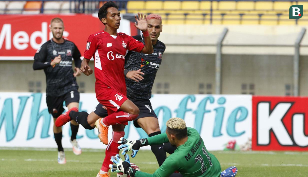 Penjaga gawang Madura United, Muhammad Ridwan berhasil mengamankan bola dari ancaman pemain Persik Kediri dalam laga Grup C Piala Menpora 2021 di Stadion Si Jalak Harupat, Bandung, Sabtu (3/4/2021). (Bola.com/Ikhwan Yanuar)