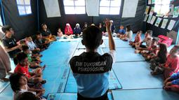 Seorang tim dukungan Psikososial bermain bersama anak-anak korban gempa tsunami Palu di halaman kantor Dinas Sosial Palu, Sulawesi Tengah, Sabtu (6/10). Trauma healingdilakukan agar anak-anak kembali ceria. (Liputan6.com/Fery Pradolo)
