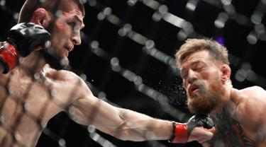 Khabib Nurmagomedov (kiri) meninju Conor McGregor dalam pertarungan UFC 229 di Las Vegas, AS (6/10). Nurmagomedov mengalahkan McGregor dan berhasil keluar sebagai pemenangnya. (AP Photo/John Locher)