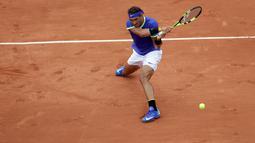 Petenis Spanyol, Rafael Nadal mengembalikan bola ke arah lawannya petenis Prancis, Benoit Paire pada babak pertama Prancis Terbuka  di Stade Roland Garros, Senin (29/5). Nadal mengalahkan tuan rumah dengan skor 6-1, 6-4, 6-1. (AP Photo/Petr David Josek)