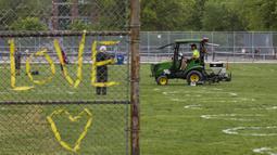 Pekerja menggambar lingkaran putih di Taman Trinity Bellwoods, Toronto, Kanada, Kamis (28/5/2020). Taman Trinity Bellwoods digambari lingkaran-lingkaran putih sebagai proyek uji coba untuk mendorong warga melakukan jaga jarak fisik (physical distancing) selama pandemi COVID-19. (Xinhua/Zou Zheng)