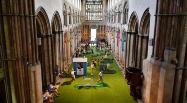 Orang-orang bermain di lapangan golf kecil yang didirikan  di dalam Katedral Rochester, Inggris pada 6 Agustus 2019. Lapangan golf ini membentang di sepanjang lorong dan memiliki sembilan lubang dengan miniatur jembatan.  (Ben STANSALL / AFP)