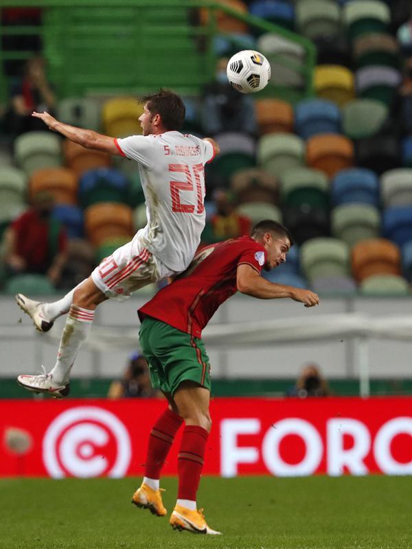 Bek Spanyol, Sergi Roberto berebut bola dengan penyerang Portugal, Andre Silva pada pertandingan persahabatan di stadion Jose Alvalade di Lisbon, Rabu (7/10/2020). Spanyol bermain imbang 0-0 atas Portugal. (AP Photo/Armando Franca)