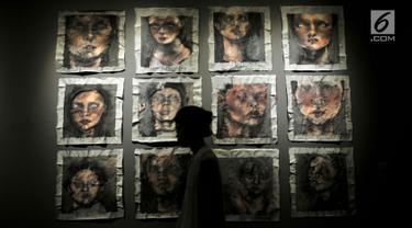 """Pengunjung melintasi lukisan karya Galuh Anindita Wardana berjudul 'And When You Took Me Fishing You Never Me Bait' di Manifesto 6.0 """"Multipolar: Seni Rupa 20 Tahun Setelah Reformasi"""" di Galeri Nasional, Jakarta, Senin (7/5). (Merdeka.com/Iqbal Nugroho)"""