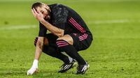 Penyerang Real Madrid, Karim Benzema, tampak kecewa usai gagal mengalahkan Elche pada laga Liga Spanyol di Stadion Manuel Martinez Valero, Rabu (30/12/2020). Kedua tim bermain imbang 1-1. (AP/Jose Breton)