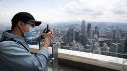 Seorang turis dengan mengenakan masker mengambil gambar dari dek obseravsi di Menara Kuala Lumpur di Kuala Lumpur, Rabu (1/7/2020). Malaysia memasuki pelonggaran Perintah Kontrol Gerakan (MCO) setelah tiga bulan pembatasan karena virus corona Covid-19. (AP Photo/Vincent Thian)