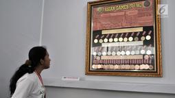 Pengunjung melihat koleksi medali yang diraih atlet Indonesia pada Asian Games 1962 dalam pameran Asian Games di Museum Fatahillah, Kota Tua, Jakarta, Selasa (14/8). (Merdeka.com/Iqbal Nugroho)