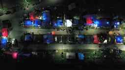 Foto udara menunjukkan tenda-tenda di tempat penampungan darurat di Mamuju (19/1/2021).  Ratusan jiwa telah mengungsi di sejumlah posko pengungsian karena rumah mereka rusak akibat gempa. (AFP/Adek Berry)