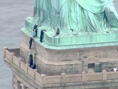 Petugas kepolisian membujuk seorang wanita yang memanjat Patung Liberty di New York, Rabu (4/7). Aksi wanita bernama Therese Okoumou ini memprotes kebijakan imigrasi pemerintah Presiden Donald Trump yang memisahkan keluarga migran. (AFP/PIX11 News/HO)