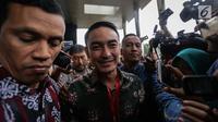 Gubernur Jambi Zumi Zola dikawal pria berseragam batik meninggalkan Gedung KPK seusai menjalani pemeriksa, Jakarta, Jumat (5/1). Zumi hanya memberikan senyuman saat dikerubungi awak media yang mengajukan pertanyaan. (Liputan6.com/Faizal Fanani)