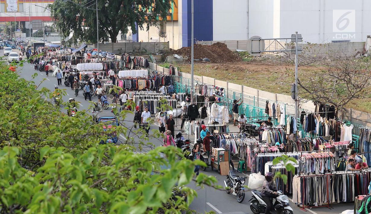 Pemandangan saat pedagang pakaian bekas berjualan di sepanjang trotoar kawasan Senen, Jakarta, Jumat (4/5). Sebagian besar pedagang merupakan korban kebakaran beberapa waktu lalu. (Liputan6.com/Immanuel Antonius)