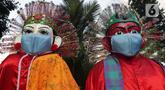 Ikon budaya Jakarta, ondel-ondel dihiasi masker wajah terpasang di trotoar Jalan Jenderal Sudirman, Jakarta, Jumat (25/6/2021). Hari ini Jumat (25/6), Provinsi DKI Jakarta mencatat penambahan kasus konfirmasi positif Covid-19 sebanyak 6.934 orang. (Liputan6.com/Helmi Fithriansyah)