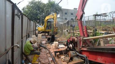 Alat berat mengeruk galian pipa instalasi proyek Sistem Penyediaan Air Minum (SPAM) di kota Tangerang Selatan, Banten, Rabu (22/07/2020). Proyek penyediaan air bersih yang memiliki kapasitas memproduksi 200 liter air per detik ini diperkirakan akan beroperasi pada 2021. (merdeka.com/Dwi Narwoko)