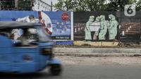 Kendaraan melintasi mural bertemakan Imbauan Protokol Kesehatan Covid-19 di kawasan Bukit Duri, Jakarta, Minggu (25/10/2020). Gubernur DKI Anies Baswedan kembali memperpanjang pelaksanaan PSBB masa transisi sebagai antisiapsi lonjakan kasus virus corona Covid-19. (merdeka.com/Iqbal Nugroho)