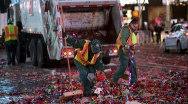 Petugas kebersihan membersihkan sampah yang berserakan di jalan usai perayaan tahun baru 2016 di Times Square di Manhattan borough, New York, USA (1/1/2016). (REUTERS/Andrew Kelly)