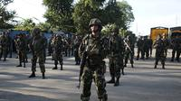 Tentara Nikaragua berjaga di luar gedung bea cukai di perbatasan antara Nikaragua dan Kosta Rika, Minggu (15/11). Nikaragua menutup perbatasannya dengan Kosta Rika hingga menyebabkan ribuan orang yang menuju Amerika terlantar. (REUTERS/Oswaldo Rivas)