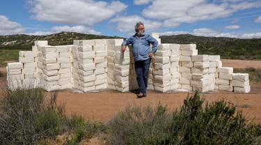 Seniman Kanada, Cosimo Cavallaro berpose sambil membangun dinding perbatasan menggunakan keju di perbatasan Amerika dan Meksiko, dekat Tecate, California, 28 Maret 2019. Cosimo menggunakan 200 blok dari keju cotija yang sudah kedaluwarsa, dan memiliki panjang sekitar 7,6 meter. (REUTERS/Mike Blake)
