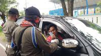 Anggota gugus tugas penanganan Covid-19 saat memeriksa KTP pelintas di posko perbatasan Sulbar-Sulsel tepatnya di Desa Paku, Binuang, Polman (Liputan6.com/Abdul Rajab Umar)