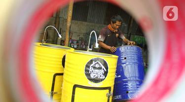Perajin memproduksi wastafel portabel berbahan baku drum di workshop Galuh Creatives, Tangerang Selatan, Sabtu (30/5/2020). Wacana pemerintah menerapkan tatanan normal baru berimbas pada meningkatnya pesanan wastafel portabel untuk kebutuhan masyarakat di wilayah Jabotabek. (merdeka.com/Arie Basuki)
