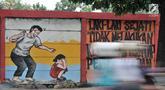 Pengendara melintasi mural bertema 'Tolak Kekerasan Perempuan dan Pelecehan Seksual' di kawasan Jatinegara, Jakarta, Senin (17/12). Mural tersebut dibuat untuk meningkatkan kesadaran akan ancaman bahaya pelecehan seksual. (Merdeka.com/Iqbal S. Nugroho)