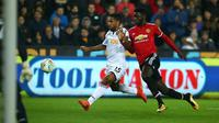 Pemain Manchester United, Axel Tuanzebe berebut bola dengan gelandang  Swansea City, Wayne Routledge pada pertandingan Piala Liga Inggris di Liberty Stadium, Rabu (25/10). MU sukses menekuk Swansea City dengan skor 2-0. (GEOFF CADDICK/AFP)