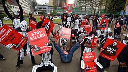 Aktivis lingkungan membawa poster penolakan saat demonstrasi menentang rencana pemerintah untuk menambang batu bara dan membuka PLTU, Nairobi, Kenya, Selasa (5/6). Aktivis mengatakan proyek itu akan berdampak buruk pada lingkungan. (AP Photo/Ben Curtis)