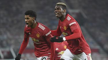 Penyerang Manchester United, Marcus Rashford (kiri) berselebrasi dengan rekannya Paul Pogba setelah mencetak gol pada menit 90+4 ke gawang Wolverhampton Wanderers pada pertandingan lanjutan Liga Inggris di Stadion Old Trafford, Rabu (30/12/2020). MU menang 1-0. (Michael Regan, Pool via AP)