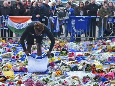 Pemain Leicester City, Darnell Johnson memberi penghormatan kepada korban kecelakaan helikopter yang menewaskan pemilik Leicester City Vichai Srivaddhanaprabha di luar Stadion King Power, Inggris, Senin (29/10). (Paul Ellis/AFP)