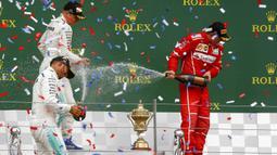 Lewis Hamilton bersama Valterri Bottas dan Kimi Raikkonen melakukan selebrasi di atas podium Sirkuit Silverstone, Minggu (16/7/2017). Pebalap asal Inggris itu melahap 51 lap dengan catatan waktu 1 jam 21 menit 27,430 detik. (EPA/Geoff Caddick)