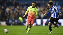Gelandang Manchester City, Bernardo Silva, berebut bola dengan striker Sheffield Wednesday, Fernando Forestieri, pada laga babak kelima Piala FA di Hillsborough Stadium, Rabu (4/3) malam waktu setempat. Manchester City menang 1-0 atas Sheffield. (AFP/Paul Ellis)