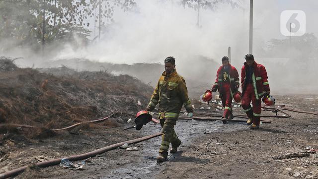 Petugas pemadam kebakaran berjalan usai memadamkan api di lapak ban bekas, Desa Bojong Nangka, Gunung Putri, Bogor, Kamis (22/4/2021). Kebakaran lapak ban bekas yang terjadi Senin (19/4) petang tersebut hingga saat ini belum bisa dipadamkan. (Liputan6.com/Herman Zakharia)