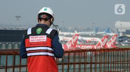 Pekerja mengenakan pelindung wajah saat mengerjakan proyek pembangunan integrated building Bandara Internasional Soekarno-Hatta, Tangerang, Banten, Rabu (29/7/2020). Pembangunan gedung penghubung stasiun Bandara Soetta dan jembatan diperkirakan rampung  akhir tahun 2020. (merdeka.com/Dwi Narwoko)
