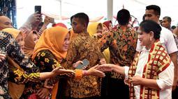 Ibu Negara Iriana Joko Widodo bersalaman dengan masyarakat saat acara penyerahan 1.300 sertifikat hak atas tanah untuk masyarakat di Kabupaten Lampung Tengah, Jumat (23/11). (Liputan6.com/HO/Biropers)