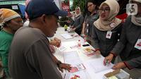 Petugas melayani para pedagang saat pembagian Kartu Pedagang di Pasar Induk Beras Cipinang, Jakarta, Rabu (20/11/2019). Kartu Pedagang dapat dipergunakan sebagai kartu identitas, kartu ATM, Jakcard Bank DKI, alat retribusi dan pengajuan kredit yang telah terekam di rekening. (Liputan6.com/HO/Budi)