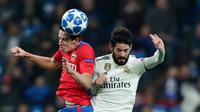 Pemain CSKA Moscow Kristijan Bistrovic melompat untuk berebut bola dengan bola gelandang Real Madrid, Isco pada laga terakhir Grup G Liga Champions di Santiago Bernabeu, Rabu (12/12). Real Madrid dipecundangi CSKA Moscow 0-3. (AP/Manu Fernandez)