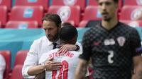 Pelatih Timnas Inggris, Gareth Southgate, memeluk Raheem Sterling setelah laga kontra Kroasia, di Stadion Wembley, Minggu (13/6/2021). (Frank Augstein / POOL / AFP)