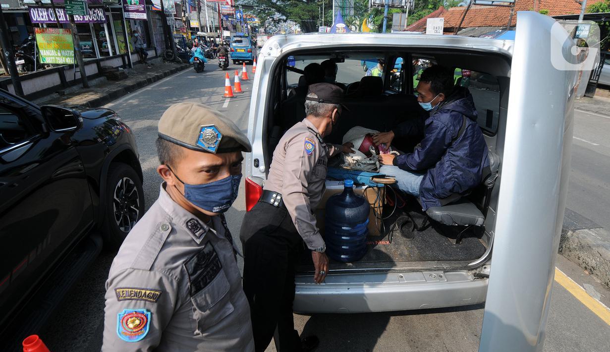 Petugas memeriksa kendaraan yang melintas di check point penyekatan arus mudik di kawasan Pasar Mudik, Bogor, Jumat (7/5/2021). Penyekatan pemudik pada jalur alternatif Parung diberlakukan jelang Lebaran guna mengantisipasi risiko peningkatan kasus COVID-19. (merdeka.com/Arie Basuki)