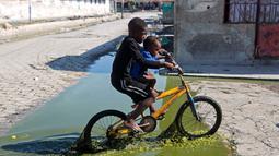 Dua anak melewati genangan air limbah saat naik sepeda melewati daerah Cite Soleil di Port-au-Prince, Haiti (17/3). Cite Soleil awalnya dikembangkan sebagai kota kumuh dan tumbuh hingga sekitar 200.000 hingga 400.000 penduduk. (AP Photo/Dieu Nalio Chery)