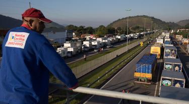 Pengemudi truk memblokir sebagian jalan, yang menghubungkan Rio de Janeiro dan Teresopolis, di Guapimirim, Brasil, Rabu (23/5). Mereka memprotes kenaikan harga solar yang terus naik selama setahun terakhir karena harga minyak dunia naik. (AP/Leo Correa)