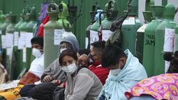 Orang-orang berkemah dengan tabung oksigen kosong mereka menunggu toko isi ulang dibuka di lingkungan San Juan de Lurigancho di Lima, Peru, Senin (22/2/2021). Kekurangan oksigen medis untuk merawat pasien COVID-19 terus menjadi norma nasional. (AP Photo/Martin Mejia)