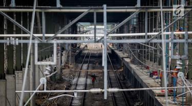 Sejumlah pekerja menyelesaikan proyek pembangunan stasiun kereta Bandara Soekarno-Hatta di Stasiun Sudirman Baru, Jakarta, Jumat (19/5). (Liputan6.com/Faizal Fanani)