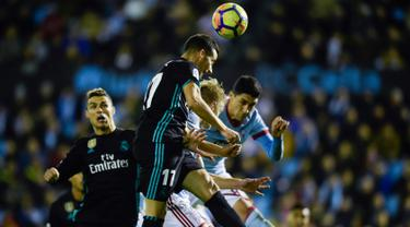 Gelandang Real Madrid Lucas Vazquez menyundul bola pada pertandingan pekan ke-18 La Liga kontra Celta Vigo di Estadio de Balaidos, Minggu (7/1). Sempat unggul berkat dua gol Gareth Bale, Madrid akhirnya harus puas dengan skor akhir 2-2. (MIGUEL RIOPA/AFP)