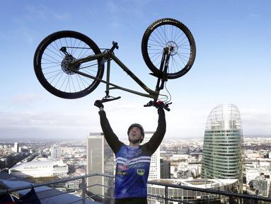 Pembalap sepeda asal Prancis, Aurelien Fontenoy, melakukan selebrasi usai berhasil mendaki 768 anak tangga dari 33 lantai gedung Trinity Tower di distrik La Defense, Paris, (17/1/2021). (AP/Christophe Ena)