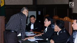Mantan hakim Mahkamah Konstitusi (MK) Patrialis Akbar (kiri) berbincang dengan kuasa hukumnya saat menjalani sidang tuntutan di Pengadilan Tipikor, Jakarta, Senin (14/8). Patrialis Akbar dituntut 12 tahun 6 bulan penjara. (Liputan6.com/Helmi Fithriansyah)