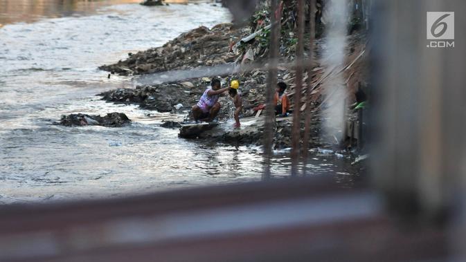 Warga memandikan anaknya di bantaran Kali Ciliwung, Jakarta, Senin (19/11). Tak adanya akses sanitasi yang layak menyebabkan anak-anak menderita stunting. (Merdeka.com/Iqbal Nugroho)