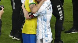Penyerang Argentina, Lionel Messi memeluk pemain Brasil, Neymar pada pertandingan final Copa America 2021 di stadion Maracana di Rio de Janeiro, Brasil, Minggu (11/7/2021). Messi, yang juara bersama Argentina, ikut menghibur Neymar. (AP Photo/Silvia Izquierdo)