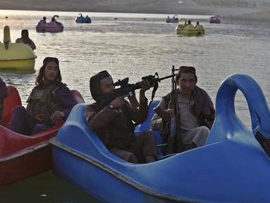 Sejumlah pasukan Taliban saat menaiki perahu kayuh di Danau Qargha di sebuah pekan raya di Kabul barat (28/9/2021). Sambil membawa senjata laras panjang sambil berjaga, mereka mengayuh perahu bebek memutari danau. (AFP/Wakil Kohsar)