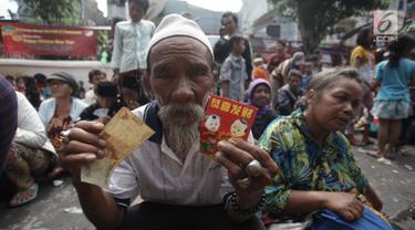 Seorang pengemis menunjukkan angpau yang didapatkan dari warga keturunan Tionghoa di Vihara Dharma Bhakti, Petak Sembilan, Jakarta Barat, Jumat (16/2). Pengemis musiman memadati Vihara Dharma Bhakti pada perayaan Imlek 2018. (Liputan6.com/Arya Manggala)